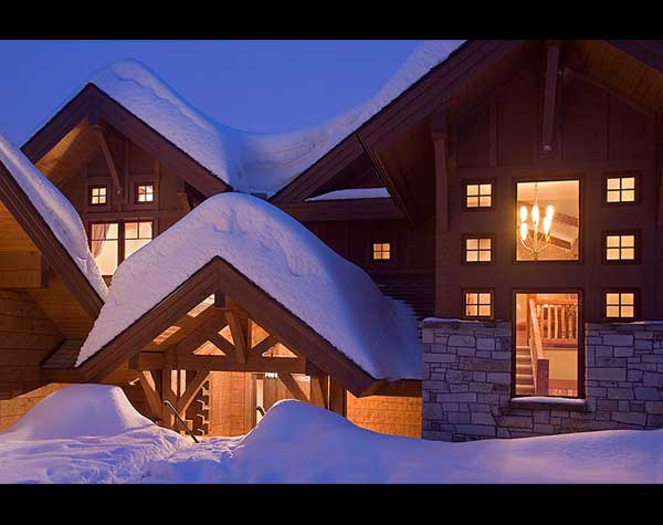 snow-covered log home dormers