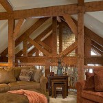 Nowhere do the Douglas fir trusses appear more striking than from the loft. Seeming to frame the natural-stone fireplace and angular windows across the great room, the timbers-all heavily adzed-bring an additional dash of grandeur to an already magnificent space.