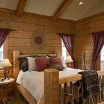Understated bedroom furnishings, including crimson window treatments and a bed as sturdy as a draft horse, match the rustic harmony found throughout the room.