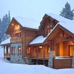 The beautiful log-and-timber hybrid home covered in snow.