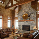 A unique blend of wood features-square, dovetailed logs on the walls and timber trusses overhead-amplifies the allure of the great room.
