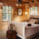 Interior designer Brian Murphy carefully chose furniture to appeal to modern aesthetics while considering the log home lifestyle. Double-hung windows in the master bedroom provide vistas of the heavily wooded lot.