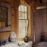 Elements such as stone tile and an antiqued metal framed mirror complement the heavy roof timbers in the main-level master bathroom.