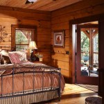 The home features identical master bedrooms (both located on the first floor), which each feature its own private walkout porch. The light color of the logs allows the knots and imperfections in the wood to show through, adding a timeworn look to the room.