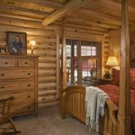 The master bedroom maintains the woodsy look, with red bedding that reflects the home's red pine logs.