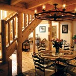 A wagon-wheel chandelier hangs above the dining area. The homeowners altered Katahdin's stock plan (shown above) to allow for a dining area behind the stairs.