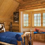Rustic log beds are found in all of the guestrooms, including this one on the third level. Beth used vibrant blue bed covers to provide a contrast to the golden hues of the log walls and tongue-and-groove ceilings.