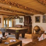 Split lodgepole pine beams add the log element to the lower level. Plush carpeting warms the floors. Dual patio doors allow abundant natural light. The cabinet and artwork are from Germany. The rustic Mission-style interior doors are custom made.