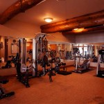 Pine beams span the ceiling of the lower-level workout room, which features commercial-grade carpet to stand up to the wear and tear of an active family.