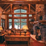 Handcrafted red pine accent trusses span the great room, while red and white pine half-logs frame the Palladian transoms in the floor-to-ceiling windows. The stone-faced fireplace, salvaged-pine floors and hand-troweled walls add textural variety.