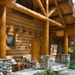 "Hand-laid stone, a majestic truss system and an arched doorway welcome guests on the front stoop. ""The home was designed to blend into the surroundings and incorporate all the amenities the homeowners were looking for,"" says Eric Gordon of Maple Island Log Homes. ""It is a wonderful design with massive log roof framing members."""