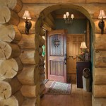 The entry showcases large handcrafted logs, wide-plank flooring and a custom-made rustic door.