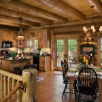 Large-diameter logs enclode the dining area and provide a backdrop for the freestanding cabinets, the knotty-pine flooring and the table and chairs. A large granite-topped island in the kitchen serves as a favorite hang-out spot for the Helsels and their three children.
