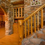 Adjacent to a built-in cabinet that stores family collectibles, cedar and black diamond willow form the spindles of the stair railing. For added visual interest, Mark incorporated the same stone surrounding the fireplace into the staircase. He then added track lighting around the base of the floor for a dramatic nighttime effect.
