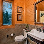 Pine clapboard substitutes for half-log wall profiles, and a pedestal sink keeps the smaller bathrooms airy and less confined.
