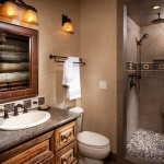 Materials with earth tones reminiscent of the Montana landscape create a serene atmosphere in the bathroom. The shower has a pebble floor to give it the appearance of a streambed. The wall sconces are adorned with honey-colored glass shades and metalwork.