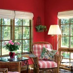 Wicker chairs with plush cushions add whimsy to the red sitting room.