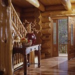 In the entrance, three different species of wood — eastern white pine logs, maple flooring, and cedar railing — set the tone for the rest of the well-detailed home.
