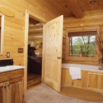 A solid pine door leads to the master bathroom, designed as a welcoming respite for homeowners with elements such as separate tiled shower, a soaking tub and a large window overlooking a wooded area. The tongue-and-groove pine used on the front of the soaking tub repeats in the interior wall, which contrasts nicely with the hickory vanity.