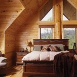 Interesting architectural angles, floor-to-ceiling windows and comfy furnishings create a lodge-like retreat for one of the upper-level guest bedrooms.