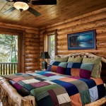 Rugged wall logs and the pine tongue-and-groove ceiling surround the master bedroom in a variety of textures. Connie selected a colorful wool and corduroy comforter for the couple's aspen log bed. Rustic cedar trims the windows and sliding patio door leading to the lakeside porch.