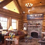 A carved eagle's head dominates the 28-by-15-foot great room above the native moss rock fireplace and red flagstone mantel. Spotlights tucked into the spruce tongue-and-groove ceiling illuminate Brian's Western art collection.