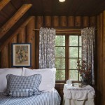 Now used as a guest room, one of the cabin's small bedrooms features gorgeous vertically stacked, round-log walls, exposed log rafters and an angled wide-plank batten ceiling—all aged to a warm honey brown.
