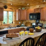 Maple cabinetry adorns the interior log walls of the kitchen, while bone-colored ceramic tile covers the main countertop and dual-level island, which provides ample room both for food prep and an eating space. The interior walls are protected with a clear polyurethane seal.