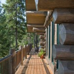 Engelmann spruce forms the massive logs. Touches of eastern log-house styling include the dark stain applied to the logs and the forest green color of the window frames. A narrow strip of deck runs across the back of the house; it connects the larger deck areas at either side.