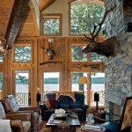 A massive stone fireplace draws attention in the great room. Windows fill the wall overlooking the lake, offering an unobstructed, breathtaking view. Red oak floors, along with outdoorsy decor, enhance the room's rustic ambiance.