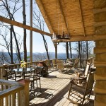 The popular rear deck provides nearly 900 square feet for family and friends to gather and enjoy sunset views or a meal prepared on the grill. Because the sloped site drops away from the deck, the space has the feel of a tree house. The knotty pine ceiling provides midday shade.