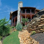 Terraced lawns bordered with dry-stack stones define the home's landscaping.