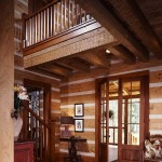 Warm colors, including crimson and mocca, invite guests into a classic home characterized by chinking between the logs and hand-planed timbers in the ceiling beams.