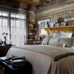 The first-floor master bedroom provides extensive views of the surrounding woodland, yet feels like the private retreat it is. Susan used an old door to create the shelf above the headboard, finding that this kind of repurposing of old pieces creates the perfect aesthetic fit for a log home.