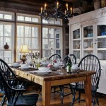 Windsor chairs, painted black, surround the antique dining table. Susan Rogers' insistence that nature take priority resulted in an interior perfectly matched to the cabin's ancient logs and recycled architectural elements.
