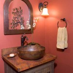 Striking red walls perfectly complement a hand-hammered copper sink, vanity base, arch mirror, round copper vessel and Tuscany vanity top in the main-level powder room.