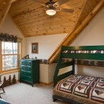 The green bunk bed and matching chests of drawers, iron sculpture and eagle wallpaper boarder highlights the North Woods decorating theme in the Walsh home. Neutral oatmeal-colored paint covers the drywall, accentuating the patina of the knotty- pine ceiling and pine accent logs.