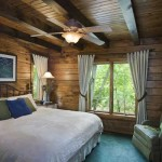 For her carpeting and decorative accents, Valerie drew upon the blues and greens of peacock feathers to highlight the warm tone of the master bedroom's log walls. The curtains are hung from sticks that Valerie collected from the property and spray-painted bronze.