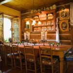 Although only Robert and Solange live in the cabin, they still have plenty of room to host guests, as the long farm table in the dining room handily shows. Robert spent many years collecting different antiques, which pepper both the tabletop and the surrounding walls.
