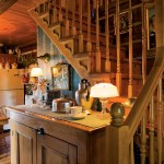 The main stairwell is placed against the cabin's lone interior log wall, which extends to the refrigerator in the kitchen.