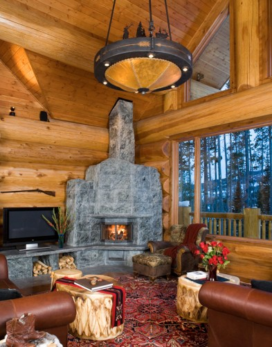 The soapstone boulders of the great room fireplace radiate heat for up to 24 hours after the fire flames out. Views of the mountain bring more of the outdoors into the living room.
