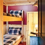 """A simplistic bunk setup provides additional sleeping quarters. Hunting gear is stored in the corner closet. """"I hunt right on the property,"""" Gregg states."""