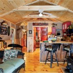 The 8-foot-tall drywall-covered interior walls of the cabin do not extend the full height of the ceiling to keep it feeling open and airy. The light brown-colored walls also prevent the space from appearing overly small. Three coats of natural-colored stain brighten the 9-inch-wide pine floor planks.
