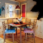 """Located on the dining table are painted """"punk"""" pieces — crafted by a local craftswoman from punk wood — that were given to Gregg in return for construction work done at the artist's home. The sleeping loft overhead, accessible via a ladder that is stored in the workshop outside, includes a carpet and futon to house an additional person."""