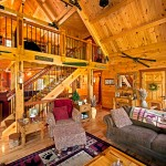 """The custom staircase is definitely a showstopper. Pete removed the original stairs and rebuilt them with heavy timbers, hand-carved newel posts and wrought iron balustrade. """"Being a log builder myself, I pride myself on a well-crafted staircase,"""" says the materials company representative. """"I feel it's a huge focal point to any log home. Pete did an outstanding job bringing his to life."""""""