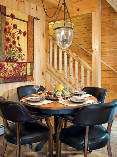 "A circular dining table for four tucks neatly into the cove created by the L-shaped staircase. After discovering they needed more room for guests, Mike built an L-shaped bench with room for eight to fit the corner. ""It's so cozy,"" says Jennifer."