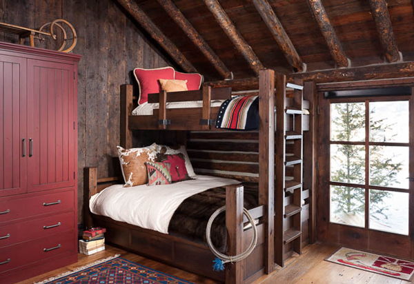 "The bunkhouse sleeps six comfortably via matching duobunk beds. ""The armoire stores extra bedding and offers hanging space for clothes,"" says the interior designer. The antique sled on top of the armoire adds instant bunkhouse charm."
