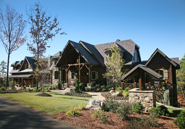 This Georgia log home creates an imposing profile. Complementing the 8-by-12-inch logs are stone turrets flanking the metal-topped, timber-framed entry,a synthetic slate roof and windows punctuated by enchanting shutters.