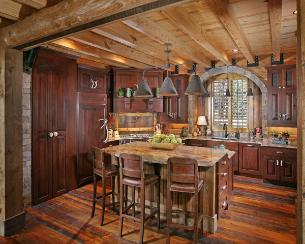 Refinished, reclaimed flooring from an old Pennsylvania warehouse highlights the roomy kitchen, whose details include antler cabinet pulls and a stone archway above the sink.
