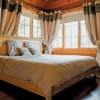 Log walls and beams sound a note of rustic romance in the master bedroom, where light and wood come together in perfect harmony. The custom pine bed was created by Maison Qisuk, the same company that built the home. It features a cherry wood base.